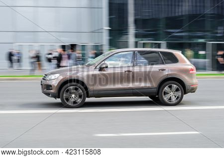 Moscow, Russia - June 2021: Profile View Volkswagen Touareg Brown Color Moving In Front Of Modern Gl