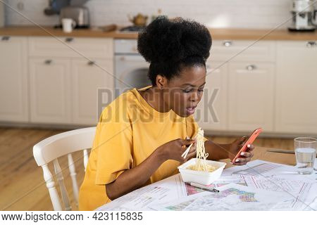 Busy Woman Use Smartphone While Having Lunch At Workplace. Overworked African Female Architect Stude