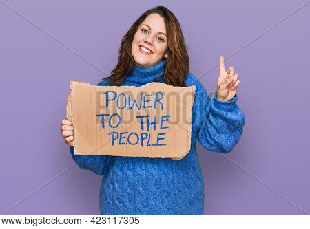 Young plus size woman holding power to the people banner surprised with an idea or question pointing finger with happy face, number one