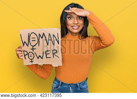 Young latin transsexual transgender woman holding woman power banner stressed and frustrated with hand on head, surprised and angry face
