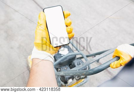 The worker holds the phone while tamping a gravel by the vibration plate. Mockup for house repair or building