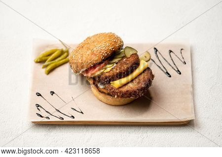Double Meat Cheeseburger Ingredients. Bun With Two Fried Cutlets, Cheese, Salted Cucumber And Tomato