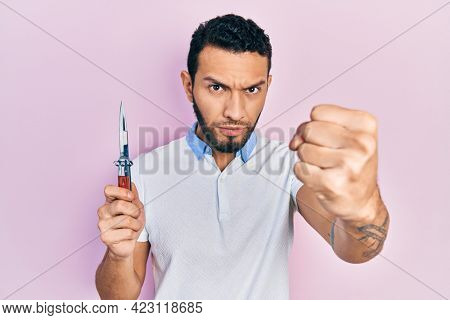 Hispanic man with beard holding pocket knife annoyed and frustrated shouting with anger, yelling crazy with anger and hand raised