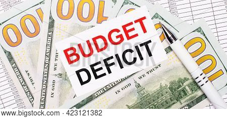 Against The Background Of Reports And Dollars - A White Pen And A Card With The Text Budget Deficit.