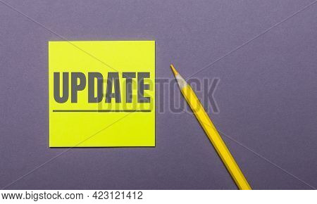 On A Gray Background, A Bright Yellow Pencil And A Yellow Sticker With The Word Update