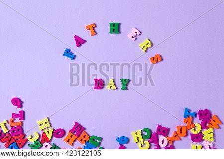 Child's Toy Letters Spelling Fathers Day Next To Randomly Lying Letters On Purple Background.