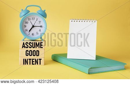 Assume Good Intentions. Inspirational Quote On Wooden Blocks With Notepad To Write On Yellow Backgro