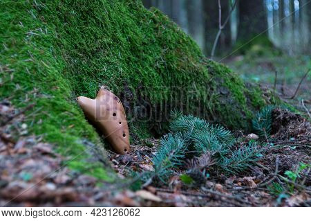 Ocarina In The Spring Forest: Ceramic Musical Wind Folk Instrument Near The Root Of A Mossy Tree And