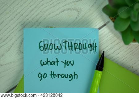 Grow Through What You Through Write On Sticky Notes Isolated On Wooden Table.