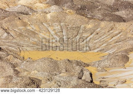 Photograph Of Crushed Sand And Stone Laying On The Ground In A Large Quarry