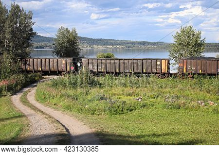 Fraser Lake, Canada - August 8, 2019: A Train Travels Along Faser Lake Carrying Coal, British Columb