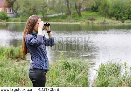Woman Birdwatcher Looking For The Bird On The Lake