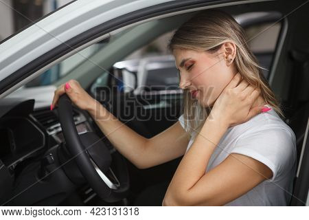 Young Woman Suffering From Neck Whiplash, Sitting In Drivers Seat Of Her Car