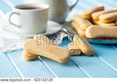 Italian cookie savoiardi. Sweet biscuits. Sponge cookies tiramisu on blue table.