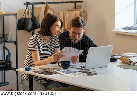 Young Tailors Work In Atelier With Laptop, Fabric Swatches On Clothes Collection Creation. Team Of D