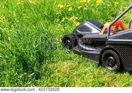 Close-up Of A Black Lawn Mower In The Backyard With Green Grass Grown Up. Garden Work Concept Backgr