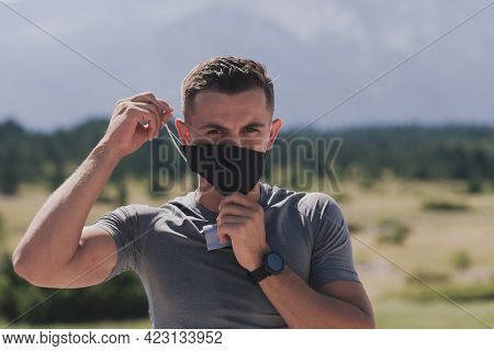 Young man and woman in protective masks running and doing exercises outdoors in the morning. Sport, Active life Jogging during quarantine. Covid-19 new normal. High quality photo. Selective focus.