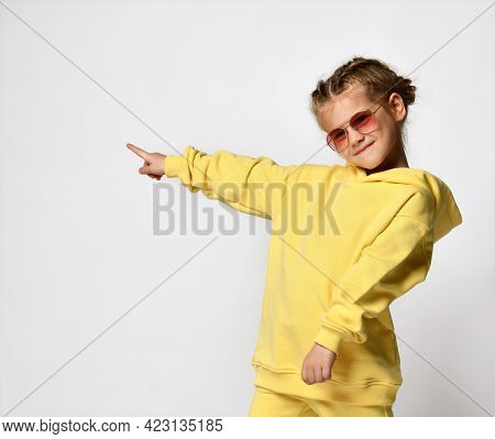 Portrait Of Active Funny Little Girl Pointing With Fingers To The Side To Free Space. Cheerful Girl,