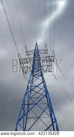High Voltage Post Or High Voltage Tower Against The Cloudy Sky In Bad Weather With Bright Lightning