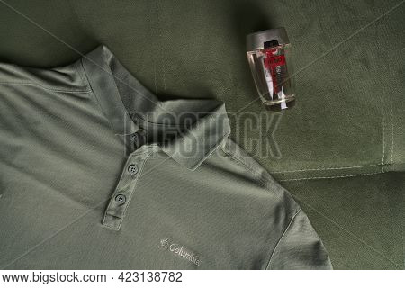 Moscow, Russia - June 8 2021: Brand Green Polo Shirt And Mens Perfume Top View. Popular Fashion Of T