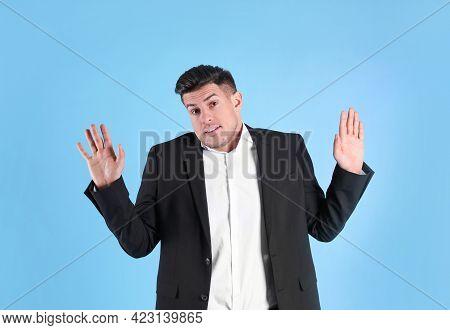 Man In Suit Avoiding Something On Light Blue Background