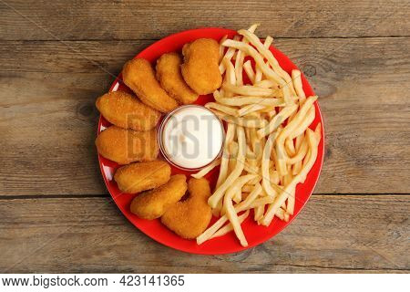 Tasty Chicken Nuggets And French Fries Served With Mayonnaise On Wooden Table, Top View