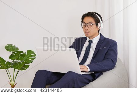 Asian Financial Advisor Wear Headphone And Glasses Use Laptop In Home Office. Businessman Work At Ho