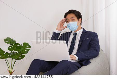 Asian Financial Advisor Wear Face Mask Headache Front Laptop On Bean Bag In Home Cafe Office. Busine