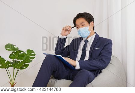 Asian Financial Advisor Wear Face Mask Serious Thinking About Customer Statement In Home Cafe Office