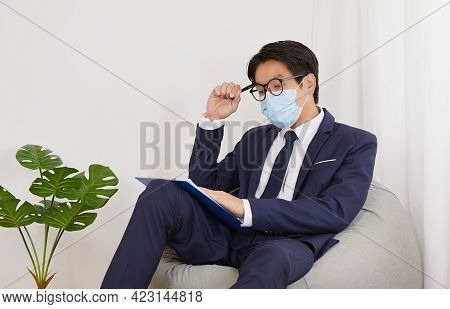 Asian Financial Advisor Wear Glasses And Face Mask Thinking Work In Home Cafe Office. Businessman Wo