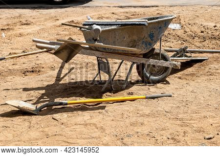 A Dirty Wheel Barrow And Other Tools, Used By A Builder To Make A Concrete Sidewalk At A Constructio