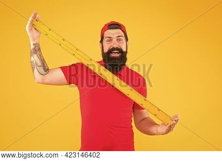 Post Office Worker With Ruler. Big Size. Measuring Tool. Man Holding Ruler On Yellow Background. Bea