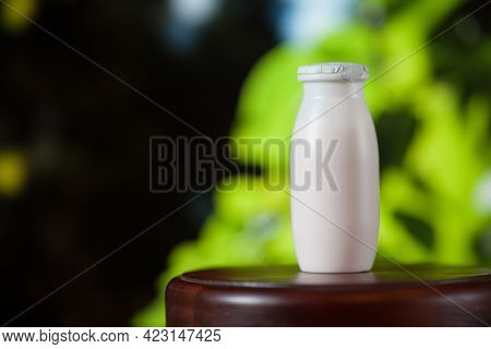 Natural Liquid Yogurt With Probiotics In Small Plastic Bottles On Wooden Table On Background Of Gree