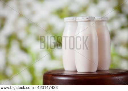 Natural Liquid Yogurt With Probiotics In Small Plastic Bottles On Wooden Table On Background Of Mead