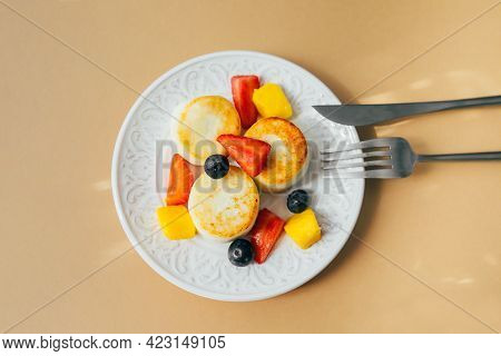 Breakfast Food Concept. Cottage Cheese Pancakes On Plate. Syrniki With Berry And Fruits On Yellow Ba
