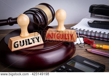 Guilty And Not Guilty Concept. Judge Cabinet And Wooden Stamps
