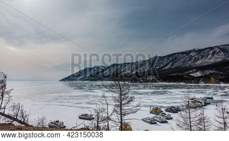 Hovercraft Are Lined Up On A Frozen Lake. Forested Mountain Range On The Background Of A Cloudy Sky.
