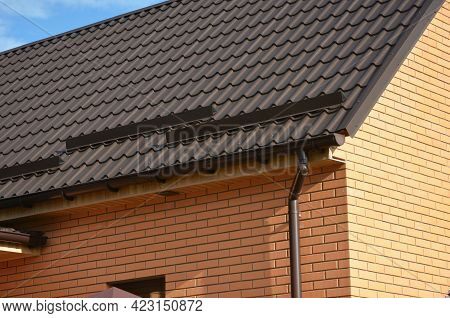 A Close-up On A Metal Brown Roof Of A Brick House With Snow Stoppers, Snow Guards, A Rain Gutter, A