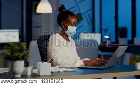 African Employee With Protection Face Mask Working At Laptop Overtime In New Normal Business Office