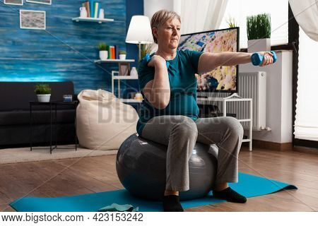 Athletic Pensioner In Sportswear Watching Online Aerobic Workout Using Tablet Sitting On Swiss Ball