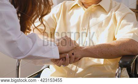 Female Nurse Doctor Wear White Uniform Holding Hand Of Patient Senior Or Elderly Old Man During Sit