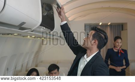 Flight Attendant Woman Service Helping Businessman Passenger To Put Luggage Suitcase Cabin Compartme