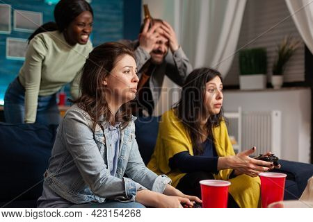Multi-ethnic Friends Sad After Losing Video Games Competition While Socialising Using Wireless Contr