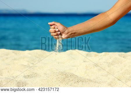 Female Hand Pours Sand On The Seashore