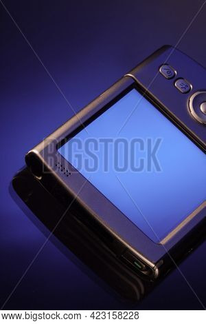 PDA smartphone on isolated blue background. Old style palm PC