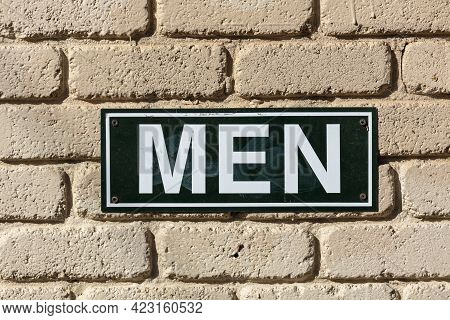 Photograph Of A Black And White Metal Men's Toilet Sign On A Light Brown Brick Wall In The Sunshine