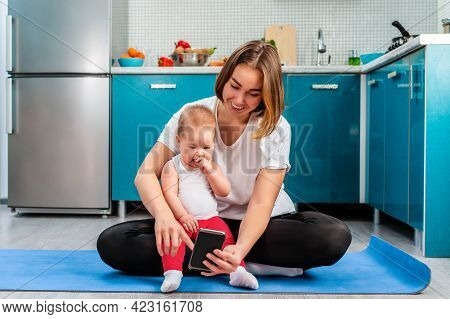 A Young Caucasian Mother Sits With Her Child On A Sports Mat And Watches Online Training Sessions On