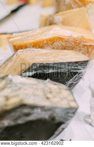 Handmade Cheese Wrapped In Polyethylene Lies On The Counter.
