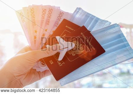 Female Hand Holds On A Background Of Sunlight, Passports With Medical Masks, Money And A Toy Plane.