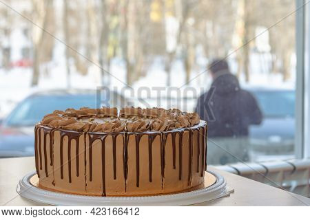 Round Chocolate Cake On A Table In A Cafe On The Background Of A Window Near The Road